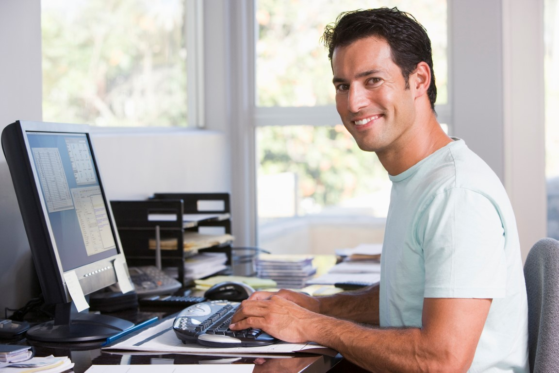 Man in home office using computer and smiling to camera