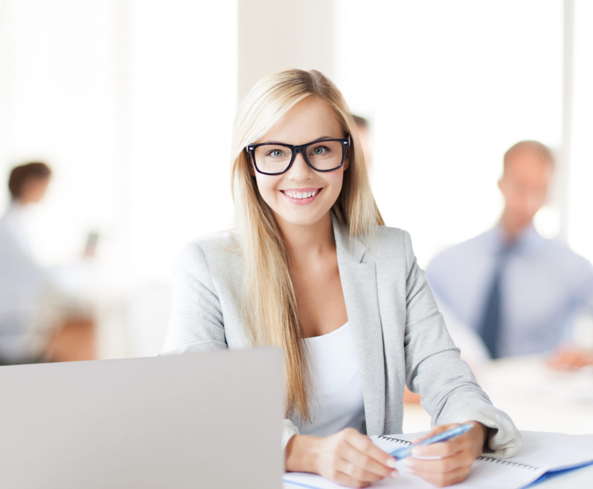 business concept - smiling woman with laptop, documents and pen in office